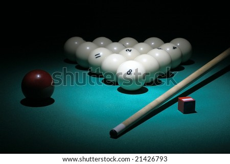 Billiard. Balls pyramid with number 8 ball of center. Selective focus on a 8ball. Floodlit scene.