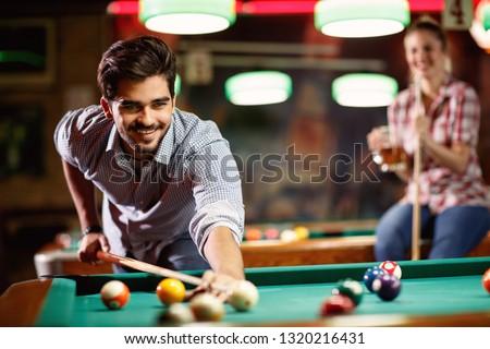 billiard game- smiling man playing snooker in club