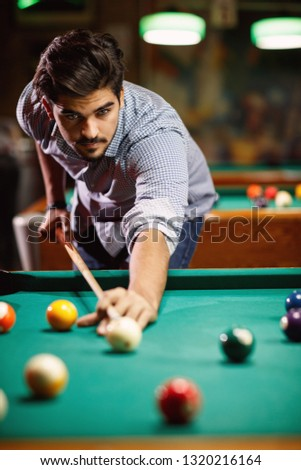 billiard game- young man playing snooker in club