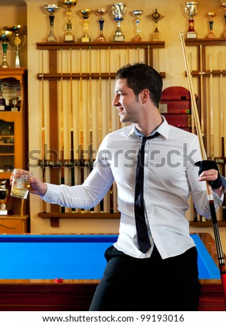 Billiard handsome young winner man with shirt tie and cue at trophy club