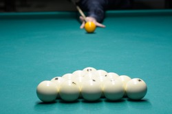 Billiard player arm breaking the pyramid by striking the ball with cue stick, beginning game