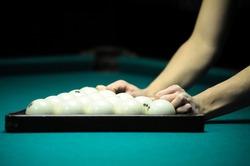 Billiard player hands set the pyramid balls to begin game