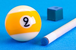 Billiard pool game nine ball with chalk and cue on billiard table with blue cloth