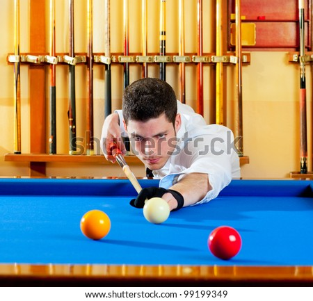 Billiard winner handsome man playing with cue and balls at club