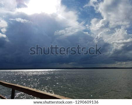 Billowing clouds with sun breaking through over glistening waters