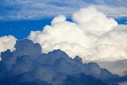BILLOWING DARK CLOUD CONTRASTING AGAINST WHITE CLOUD IN BLUE SKY