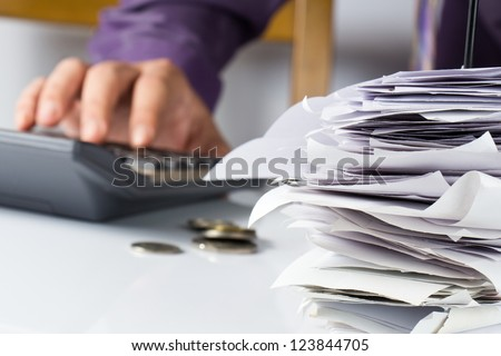 Bills in paper nail with hand calculating