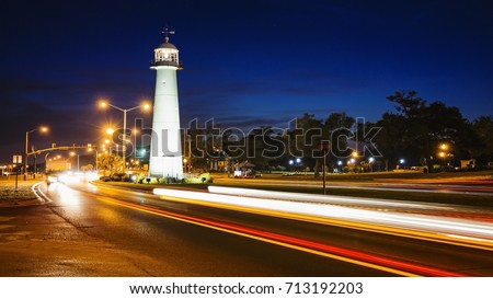 Biloxi lighthouse as night falls with passing automobile traffic in Mississippi