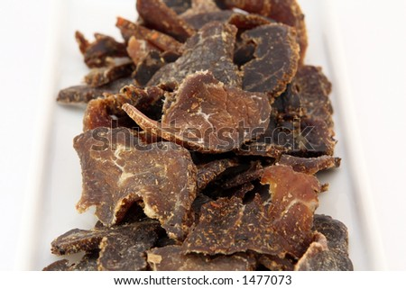 Biltong is a healthy low fat, high protein cured dry meat suitable for dieting using sun dried methods of food preservation, shallow dof, macro, on white, closeup