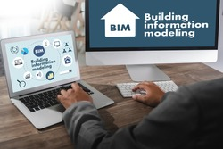 BIM Business team hands at work with financial reports BIM - Building information modeling  and a laptop
