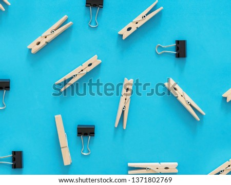 Binder clips and wooden clips on blue backgrounds