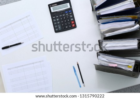 Binders with papers are waiting to be processed with bookkeeper. Internal Revenue Service inspector working place. View from above