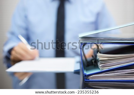 binders with papers are waiting to be processed with businessman  back in blur. Accounting and business concept