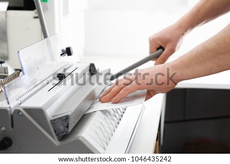 Binding documents, a man binds cards. The bookbinder binds documents. - Shutterstock ID 1046435242