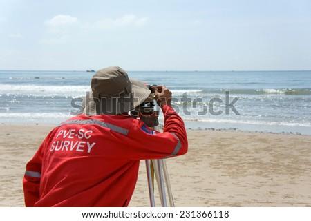 BINH THUAN, VIET NAM- OCT 21: Asian engineer work on Vietnamese beach, man looking in theodolite to survey sea level, measurement device set on tripod, Vietnam, Oct 21, 2013