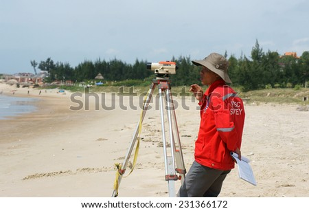 BINH THUAN, VIET NAM- OCT 21: Asian engineer work on Vietnamese beach, man looking in theodolite to survey sea level, measurement device set on tripod, Vietnam, Oct 21, 2013