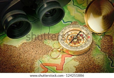 binoculars and a compass on the map with sand - stock photo