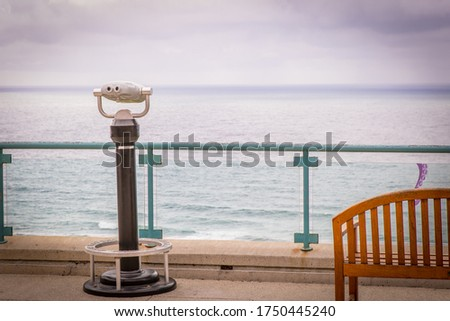 Binoculars and Bench Looking Out Over Ocean Stockfoto ©