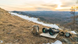Binoculars map compass and mug on the background of nature mountains in the sunset. The concept of a halt, tourism travel, trip. Navigation, route