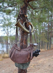 binoculars, old bag, hunting bugle hanging on a tree in the forest in autumn