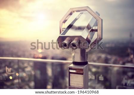 Binoculars or telescope on top of skyscraper at observation