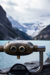 Binoculars with view to the white mountains over a lake