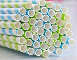 Bio degradable earth and ocean life friendly paper straws. Blue and green striped paper straws on a white surface.