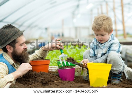 bio fertilizer. father and son put into the soil bio fertilizer. bio fertilizer production. industry production of bio fertilizer. greenery brings life to your home #1404695609