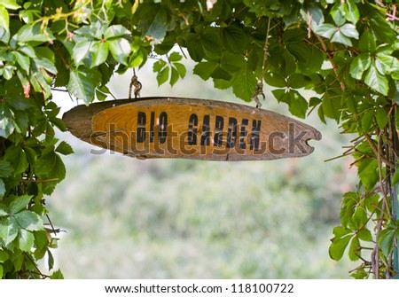 bio sign message on a wooden panel and green plant