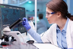 Biochemist scientist working on the laboratory to discovery a technology for a virus. Chemistry research and analysing in science medicine lab developing and stying new type of vaccin