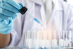 Biochemistry laboratory research, Scientist or medical in lab coat holding test tube with using reagent with drop of color liquid over glass equipment working at the laboratory.
