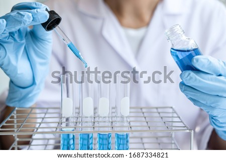 Biochemistry laboratory research, Scientist or medical in lab coat holding test tube with Using Microscope reagent with drop of color liquid over glass equipment working at the laboratory.