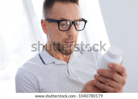 Biohacking technology. Meditative wistful unsure man putting on glasses while opening mouth and looking at bottle #1040780179