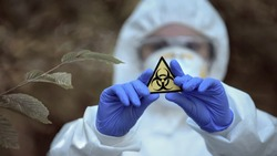 Biological hazard sign in researcher hands, health threat, virus danger, toxin