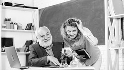 Biological research. Teacher and girl with notepad near chalkboard. Biology science. Study biology. College university education. Biologist or chemist with microscope teaching student biology.