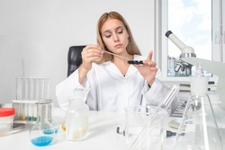 Biologist at work steel. Chemist next to microscope. Woman chemist. Female employee of chemical laboratory. Young girl works in laboratory. Portrait of laboratory technician. Biologist in white coat