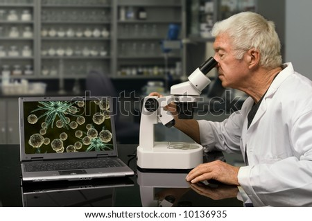 Biologist looking through a microscope in a research lab - stock photo