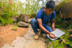 Biologist or botanist recording information about small tropical plants in forest. The concept of hiking to study and research botanical gardens by searching for information.