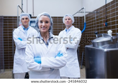 Biologist team standing smiling with arms crossed in the factory