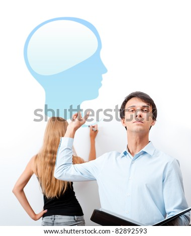 Biology or psychology lesson. Teacher giving lecture with help of his student, drawing human head and brain on white board