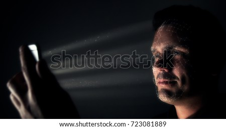 Biometric facial recognition on a smartphone. Male smiling at smartphone as it scans his face