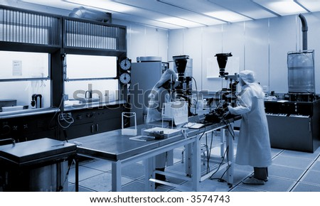 Biotech lab in cool blue with two technicians peering into microscopes in white, clean suits