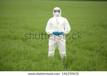 biotechnology engineer in white uniform, mask, goggles on field of genetically modified crops portrait