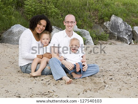 Biracial family sitting on the beach.