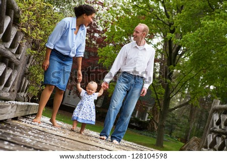 Biracial family walking along a wooden bridge.  Space for your text.