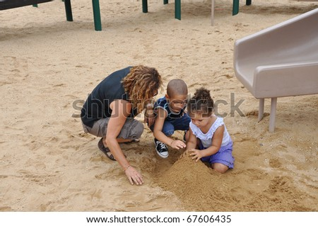 Biracial Family Woman Preschool Age Boy Toddler Girl Playing with Sand on Playground