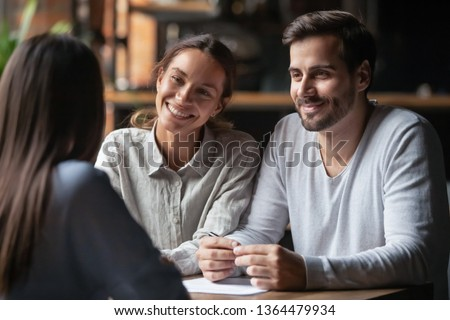 Biracial woman caucasian man listen vacancy candidate sitting together at table at job interview. Diverse couple communicating with real estate agent, successful meeting ready to sign contract concept #1364479934