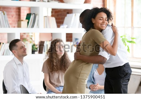 Biracial woman psychologist addiction counsellor hug afro guy at group session express support gratitude for honesty, diverse people gather together solve problems abuse struggle, rehab center concept