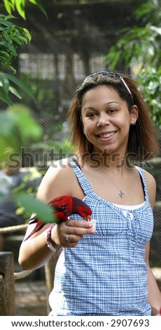 biracial young woman feeding a red (eclectus) parrot by hand