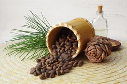 Birch bark jar with pine nuts, a branch of cedar, a cone and a bottle of cedar oil on a straw mat. Close up. Theme of healthy and healthy products.